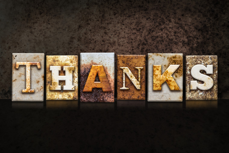 "The word ""THANKS"" written in rusty metal letterpress type on a dark textured grunge background."